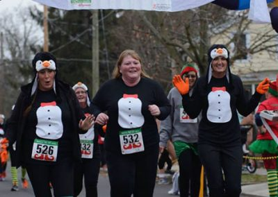 foodbankst-events-selfless-elf-group-of-women-crossing-finish-line