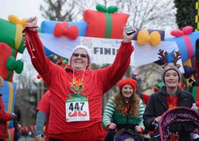 foodbankst-events-selfless-elf-happy-runners-crossing-finish-line