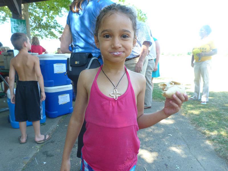 foodbankst summer food service program little girl eating a wrap - Our Programs