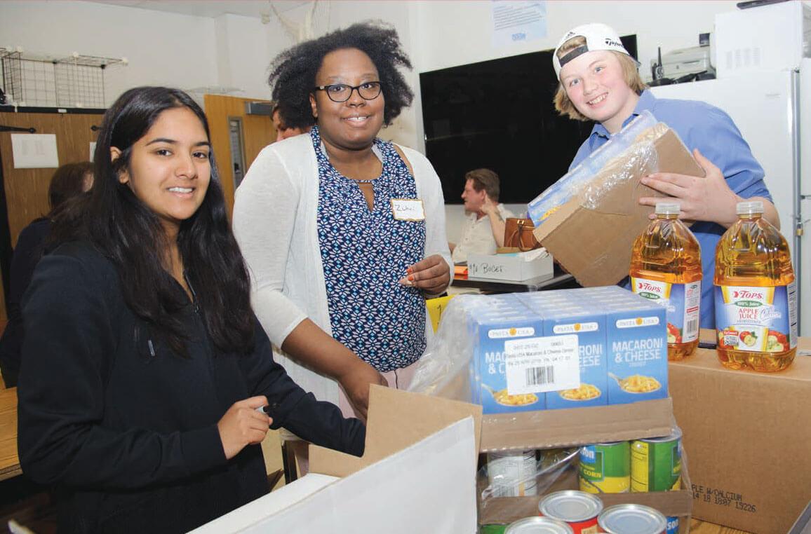 foodbankst volunteers packing food - Piloting A Pantry, Creating Community